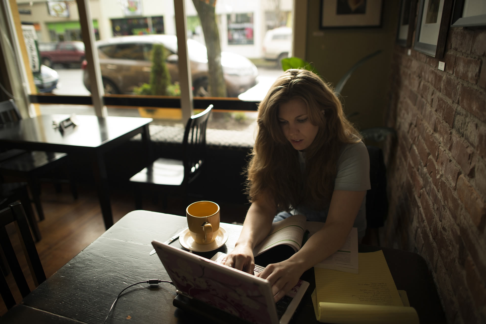A young woman working on her laptop in a coffee shop
