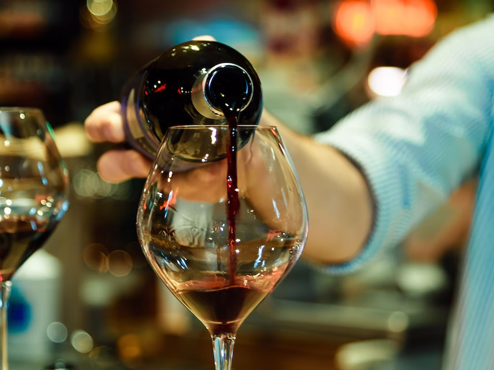 Red wine being poured into a wine glass by a bartender